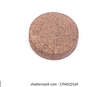 Dry peat pellets, compressed compost tablet isolated over the white background