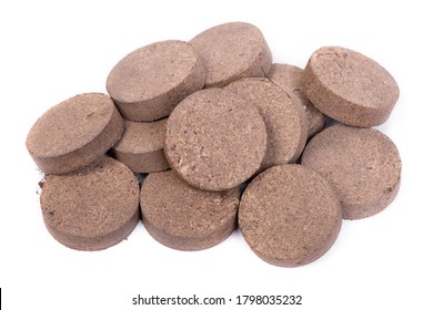 Dry peat pellets, compressed compost tablet isolated over the white