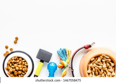 Dry pet food in bowl and toys, brushes on white background top view space for text