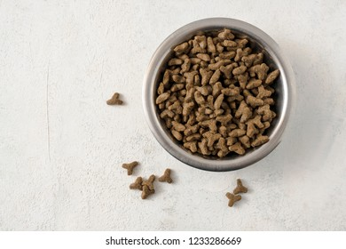 dry pet food for cats or dogs in a metal bowl on a light background with copy space, high angle view from above, selected focus