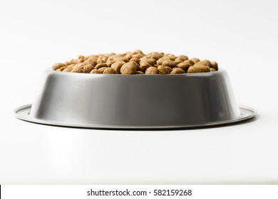 dry pet food in a metal bowl isolated on white background.