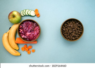 Dry pet food with natural ingredients. Raw meat, fruit and vegetables flat lay with copy space. choice between natural food and dry food