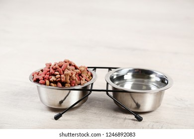 Dry pet food and water in bowls on timber flooring at home