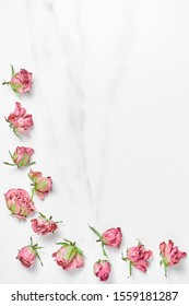 dry pink flowers on a marble background. frame lined with roses. flat layout, space for text.