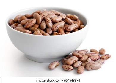 Dry pinto beans in white ceramic bowl isolated on white. Spilled beans.