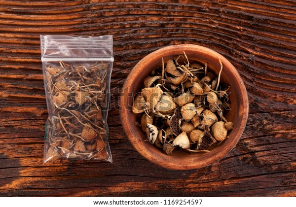 Dry psilocybin magic mushrooms in plastic bag and wooden bowl on brown table. Medical alternative remedy.