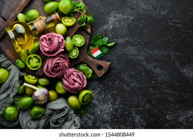 Dry purple pasta with tomatoes and parsley oil. Italian traditional cuisine. Fresh vegetables. Top view. Free space for your text.