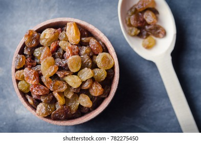 Dry raisins in a wooden bowl.