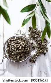 Dry raspberry leaves in a tea strainer close-up. Alternative herbal medicine. Healthy lifestyle concept. Composition with organic, natural herbal tea on a light wooden table.