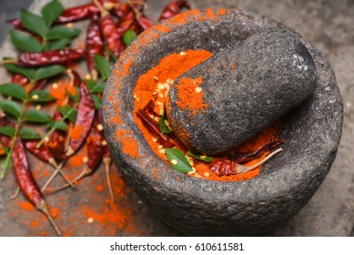 Dry red Kashmiri chilly/ chilli being crushed to powder in a traditional kitchen using vintage grinder / stone mortar, Kerala India. Indian spices for hot and spicy curry / cuisine / dish.