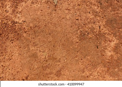 Dry red, orange soil and small rock in Thailand. This land is hard, barren, desolate, penurious, rainless, arid and drought. Plant is hard to live in this kind of soil.