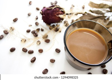 Dry red rose with coffee beans and coffee cup isolated
