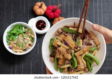 Dry rice vermicelli fried with vegetables from top view, a Vietnamese vegetarian dish for vegans, a dish can make quick for breakfast at home from noodle, vegetable, mushroom, tofu