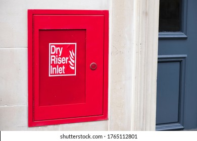 Dry riser red inlet box and sign at wall