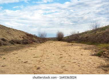 Dry river bed with only sandbanks showing , no water, drought, animal tracks in sand.