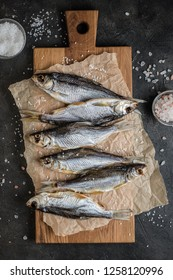 Dry salted fish on cutting board on the table