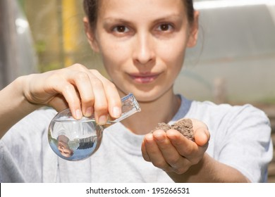 dry soil in female hand and a flask with water
