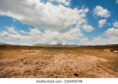 Dry soil under white clouds and blue sky. Mountains in perspective of bright sunny scene at high attitude.