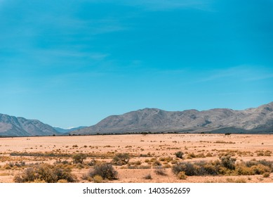 Dry South African Karoo landscape with clear blue skies and mountains in the distance