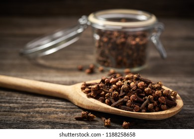 Dry spice cloves in a wooden shovel on a gray wooden background