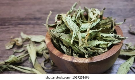 Dry Stevia on the wood bowl isolated on wood background  is a sweetener used to replace sugar. Stevia rebaudiana Bertoni