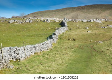 Dry stone field boundary wall  or dyke near Ingleton near the village of Thornton in Lonsdale in the North Yorkshire Dales in England UK with grass in sunny weather with blue skies and clouds
