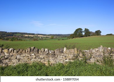 a dry stone wall in amongst agricultural scenery in the yorkshire wolds england under a clear blue sky in autumn