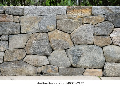 Dry stone wall and drain pipe, detail. Closeup of retaining wall between garden and sidewalk. Rounded edge fieldstone and flagstone variation, large and small, gray and brown, dry-stacked, natural.