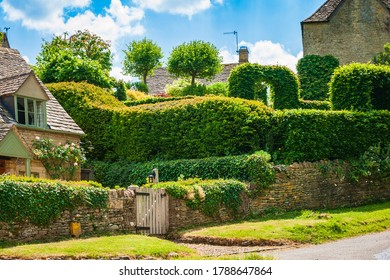 Dry stone wall fence with trimmed lush hedges and stone cottages in background. Picturesque view of an English countryside on a sunny spring day.