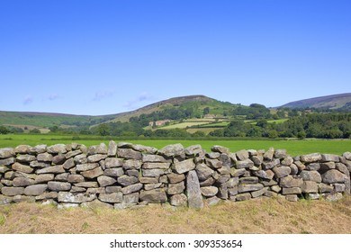a dry stone wall in front of rudland rigg on the north york moors under a blue sky in summer