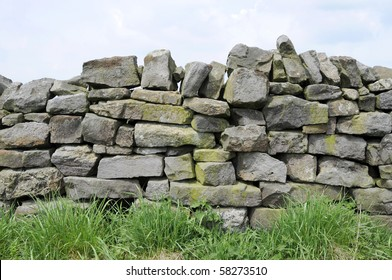 A dry stone wall made of random grey stone with grass at bottom.
