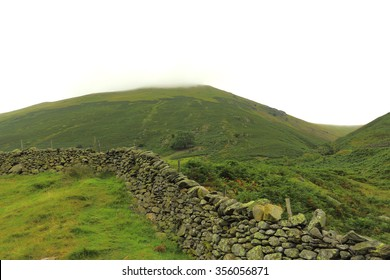 Dry stone wall or sheep rest in a pasture with misty mountain in the background.