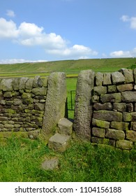 a dry stone wall with stone stile or narrow gate with steps in a yorkshire dales hillside meadow with a bright blue summer sky and sunlit grass