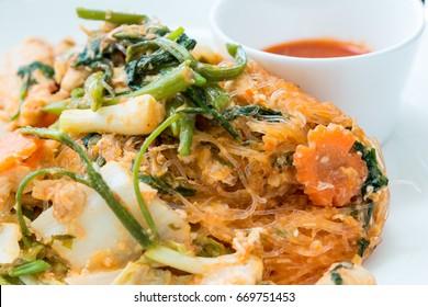 Dry sukiyaki fried vermicelli with vegetables and pork. Stir fried sukiyaki with vegetables and meats without broths. Stir fried mixed vegetable in sukiyaki sauce on plate. Healthy Food.