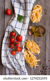 Dry tagliatelle pasta and ingredients for cooking it on wooden table