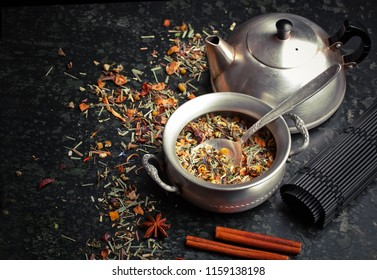 Dry tea leaves in a spoon on an old background