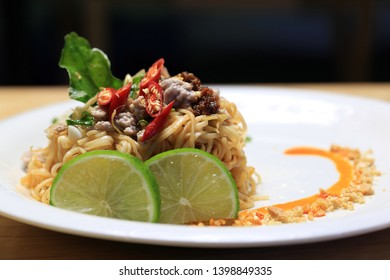 Dry Tomyum noodles in decorated white plate