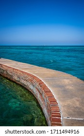 Dry Tortugas Mote Wall With Loggerhead Lighthouse in Distance on clear day