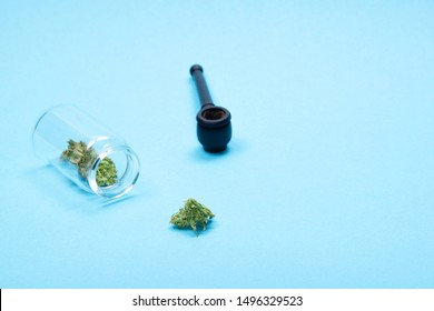 Dry trimmed medical marijuana buds in a small open glass jar and scattered aside and wooden pipe on blue  background. Alternative treatment. Medical cannabis. Copy space.
