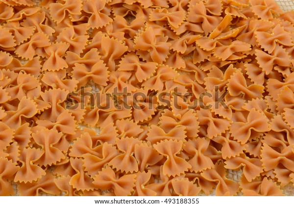 Dry uncooked carrot and squash vegetable farfalle bow tie pasta