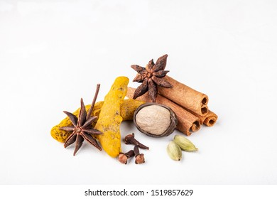 Dry warming Indian spices for autumn and winter meal on white concrete background. Exotic vitamin, flavor, alternative medicine, Ayurvedic. Turmeric, cinnamon, clove, cardamom, nutmeg, anise.