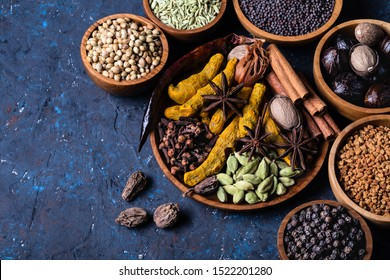 Dry warming Indian spices on plate for autumn winter meal on dark blue concrete background. Exotic vitamin, flavor, Ayurvedic. Turmeric, cinnamon, clove, cardamom, pepper, anise.