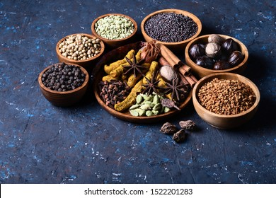 Dry warming Indian spices on plate for autumn winter meal on dark blue concrete background. Exotic vitamin, flavor, alternative medicine. Turmeric, cinnamon, clove, cardamom, pepper, anise.