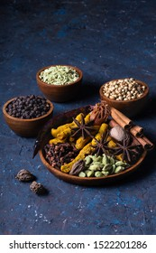 Dry warming Indian spices on plate for autumn winter meal on dark blue concrete background. Exotic vitamin, flavor, alternative medicine, Ayurvedic. Turmeric, cinnamon, clove, cardamom, pepper, anise.