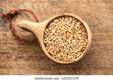 Dry wheat seeds, grains in wooden bowl