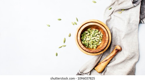 Dry whole cardamom in wooden bowl, gray background, top view