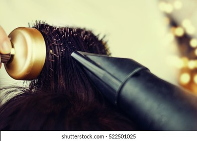 Drying brunette hair with hair dryer and round brush.