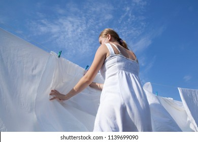 Drying clean laundry in rope outdoors on sunny day. Young girl is hung up sheets on clothesline. Strong wind blows white sheets. View from below