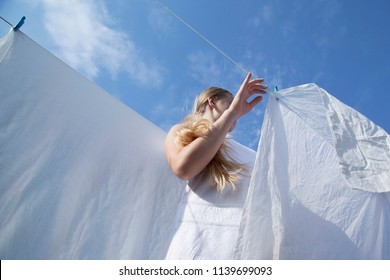 Drying clean laundry in rope outdoors. Young woman in white dress on blue sky background. Wind blows the sheets. View from below
