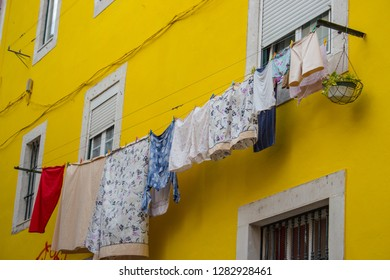 Drying clothes outside windows against yellow wall. Bright colorful building in Portugal. Traditional house exterior in Europe. Laundry on rope at the street. Fresh clothesline. Hanging drying linen.